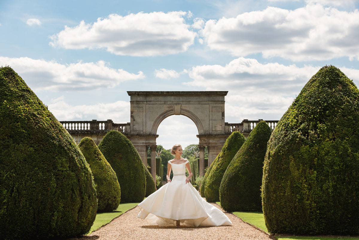 A bride walking in the Italian gardens at Castle Ashby