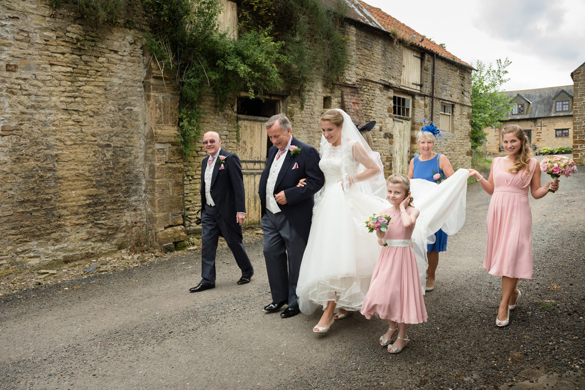 Bride walking to church with parents and bridesmaids