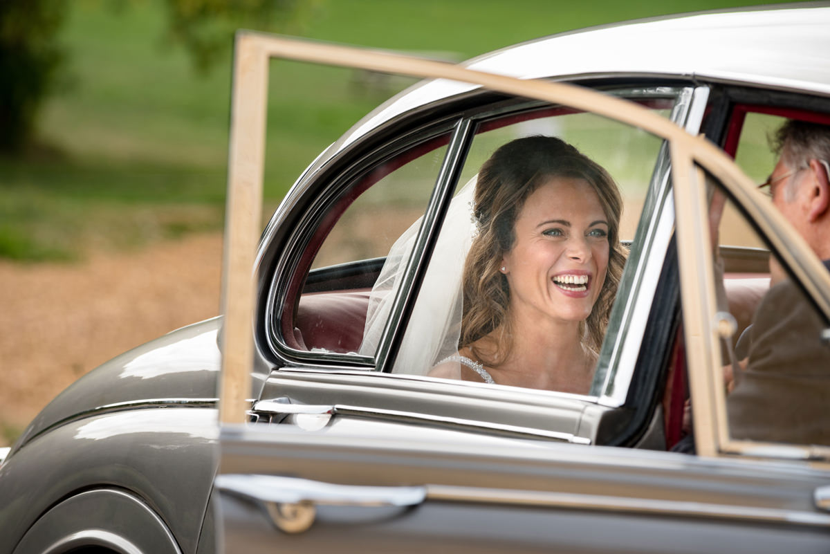 Bride laughing in wedding car