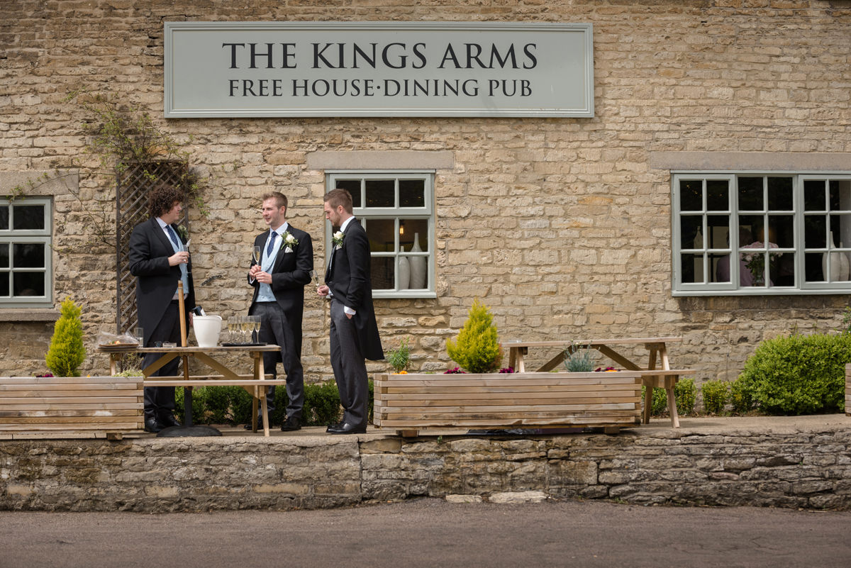 Groomsmen drinking champagne at the The Kings Arms pub in Polebrook