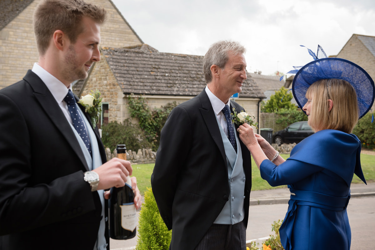 Groom's mum pinning buttonholes at the The Kings Arms pub in Polebrook