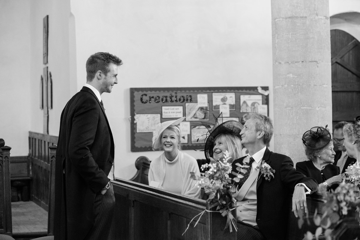 The groom laughing with his parents at All Saints church in Polebrook near Oundle