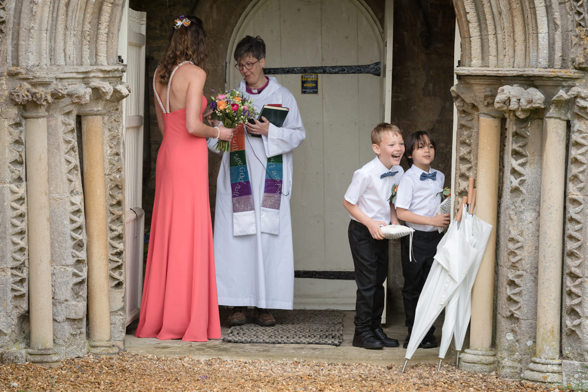 Page boys laughing while they wait for the bride at All Saints church in Polebrook near Oundle