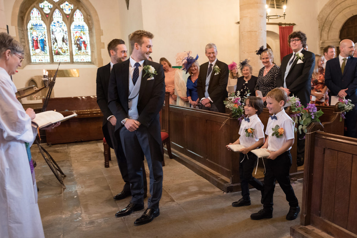 Page boys walking down the aisle at All Saints church in Polebrook near Oundle