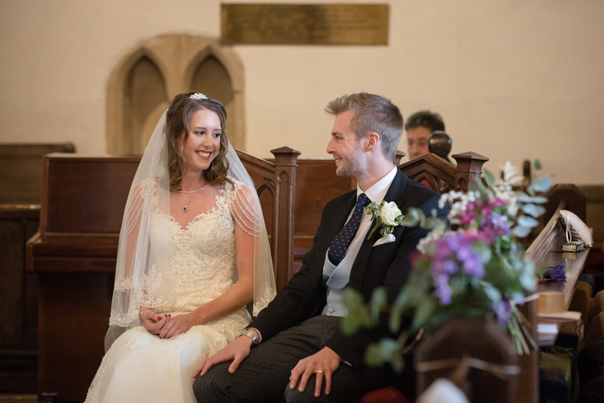 Bride and groom listening to the address at All Saints church in Polebrook near Oundle