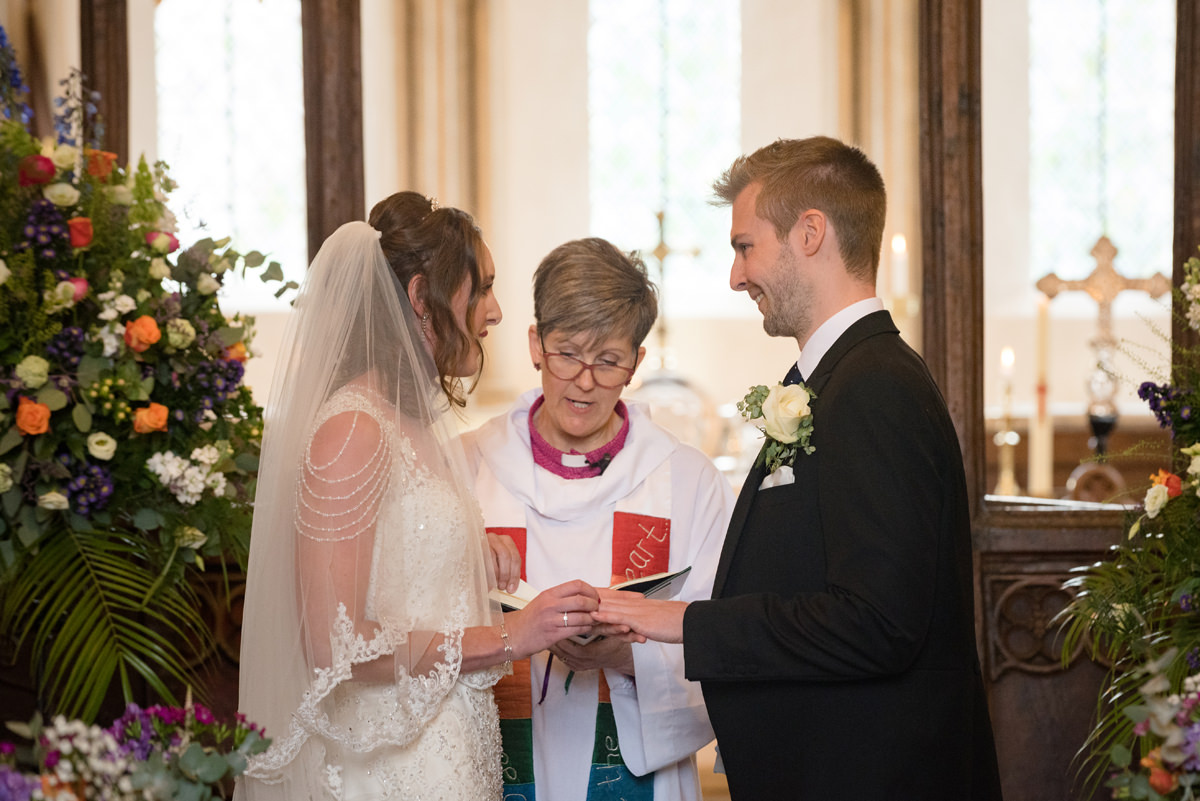 Bride and groom exchanging rings at All Saints church in Polebrook near Oundle