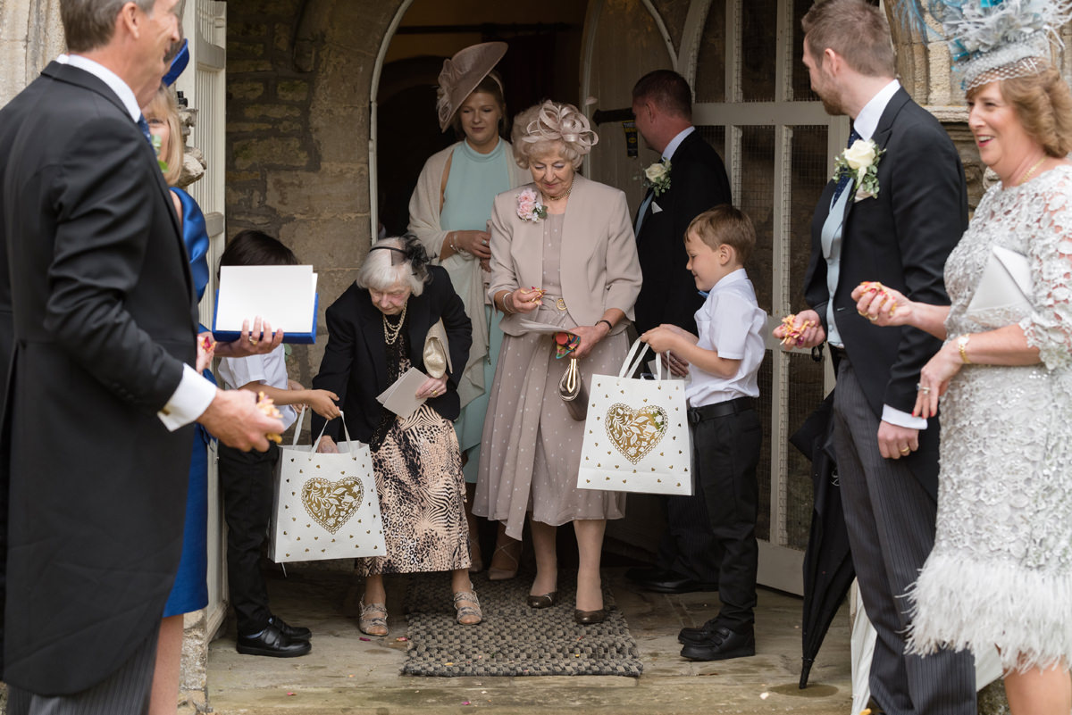 Page boys handing out confetti at All Saints church in Polebrook near Oundle