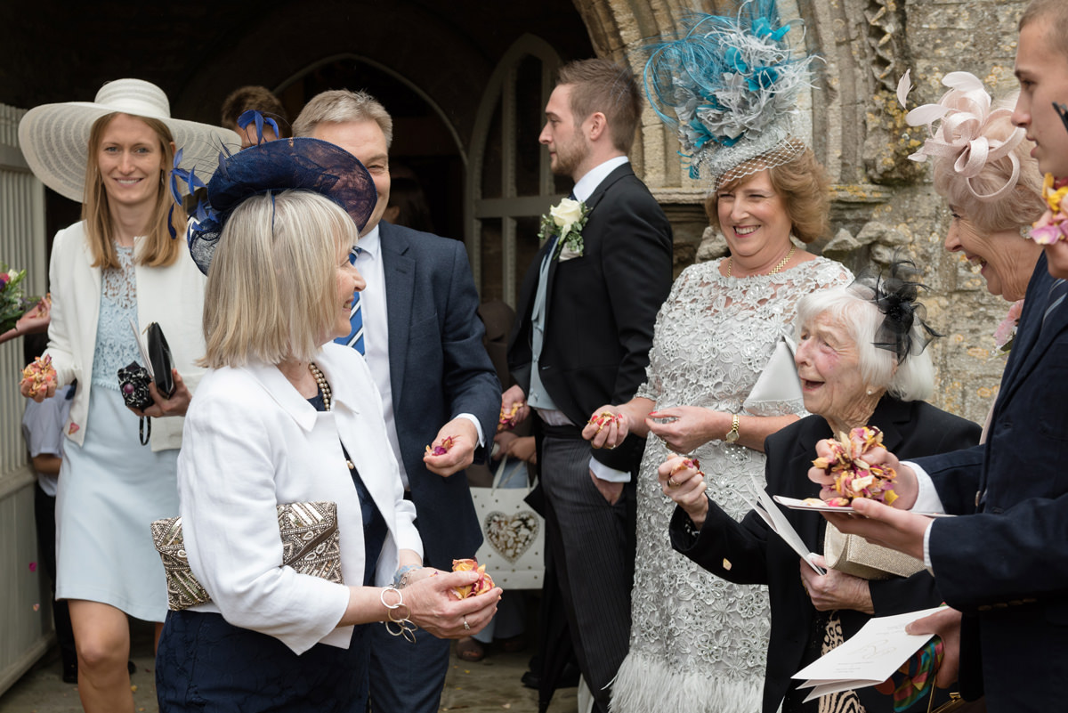 The bride's family laughing outside All Saints church in Polebrook near Oundle