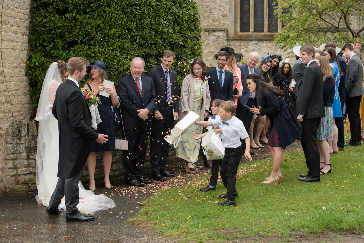 Pageboys having fun with the confetti at All Saints church in Polebrook near Oundle