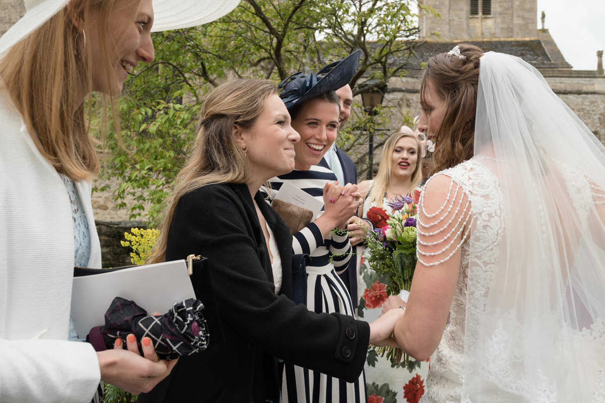 Wedding guest greeting the bride at All Saints church in Polebrook near Oundle