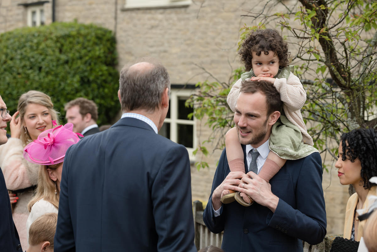 A young wedding guest sitting on Dad's shoulders at All Saints church in Polebroo