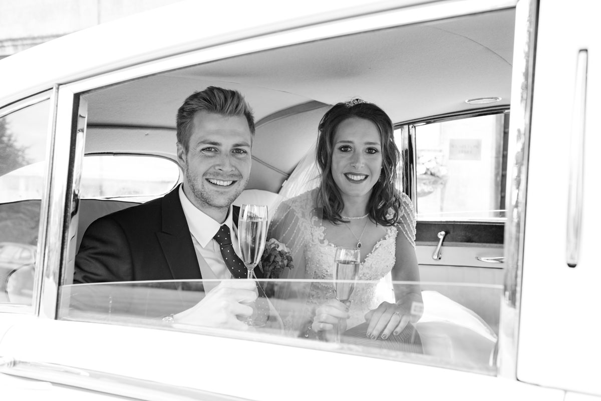 Bride and groom in the back of the wedding car at Rushton Hall in Kettering