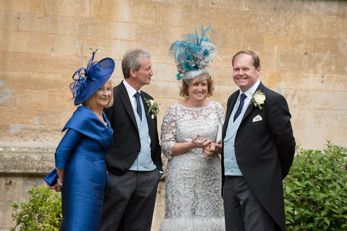 Parents of the bride and groom laughing together at Rushton Hall in Kettering