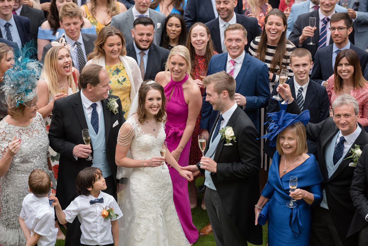 The bride and groom surrounded by their guests at Rushton Hall in Kettering