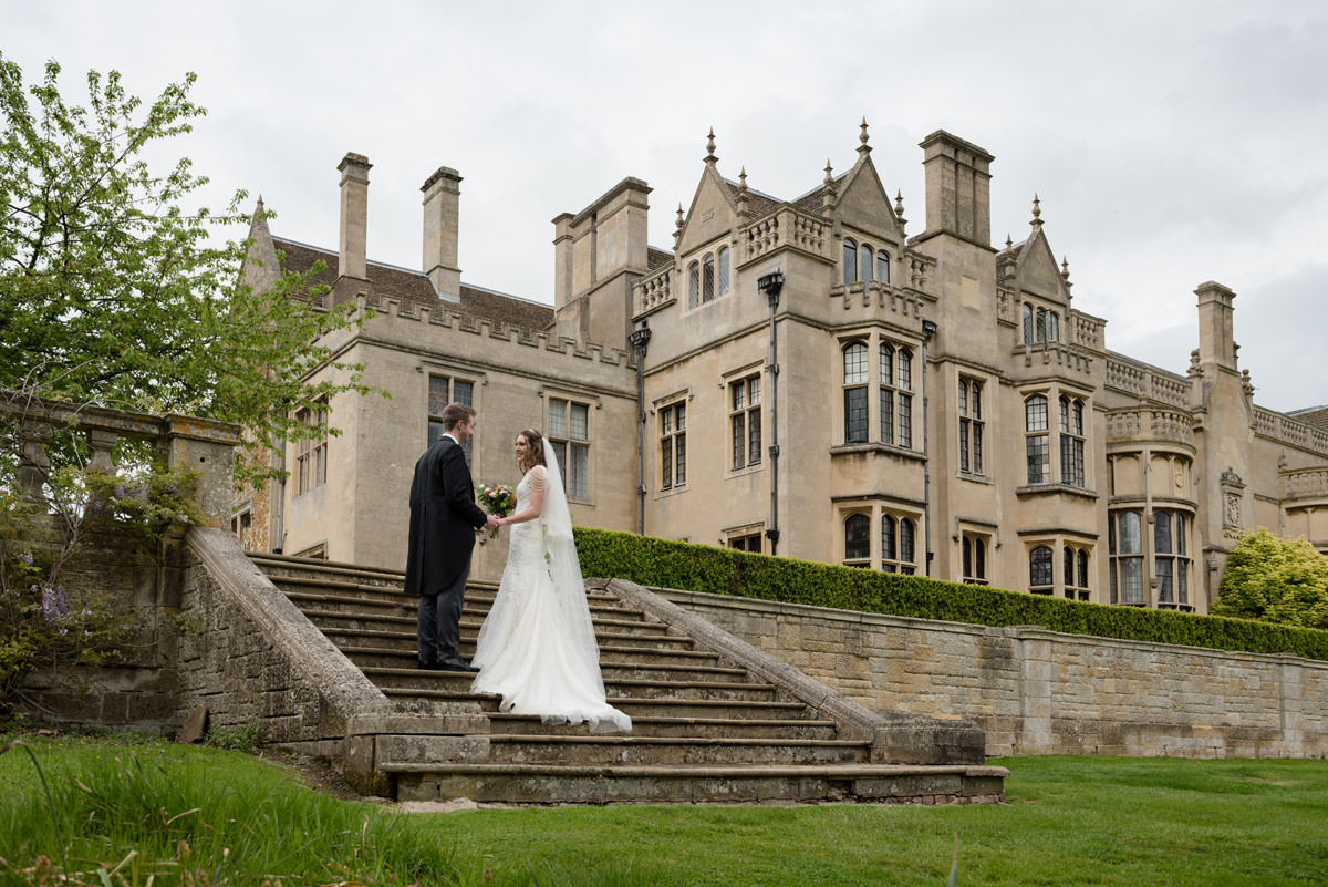 Bride and groom on the steps at Rushton Hall in Kettering