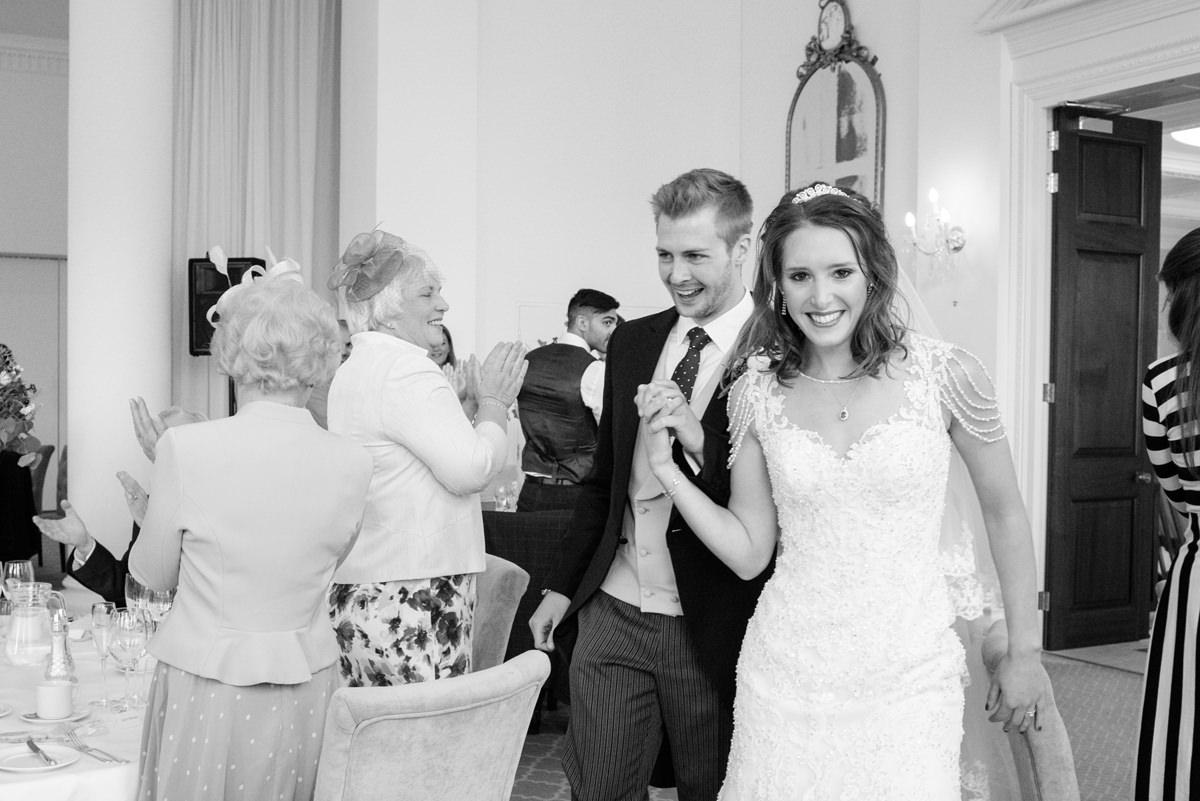 Bride and groom being announced in for dinner at Rushton Hall in Kettering