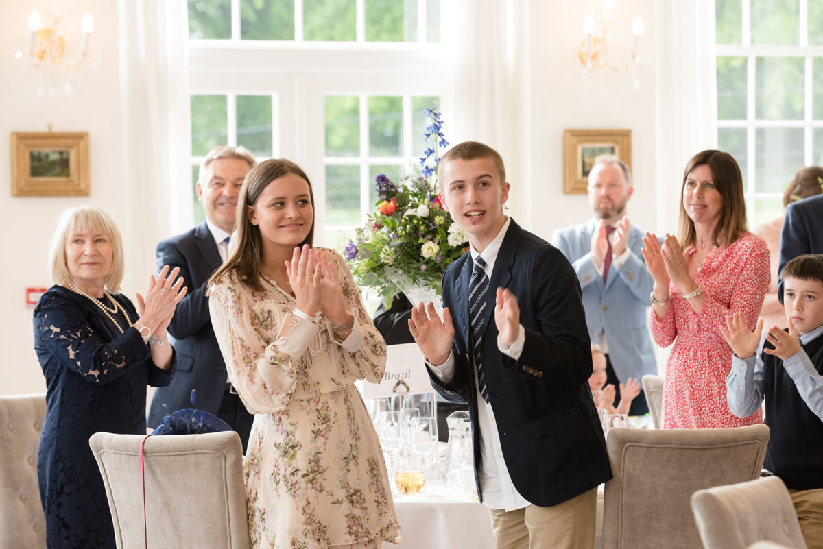 Wedding guests clapping as the couple make their entrance for dinner at Rushton Hall