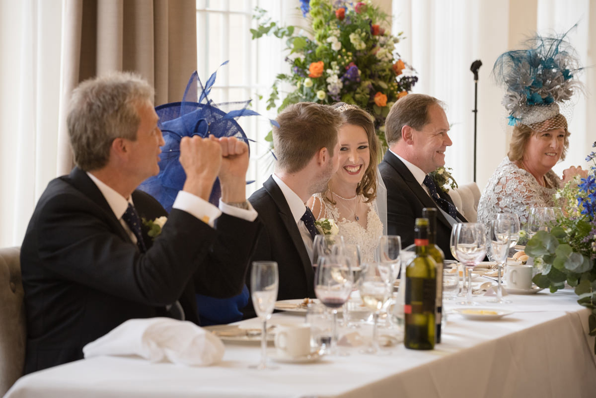 Bride laughing at singing waiters at Rushton Hall in Kettering