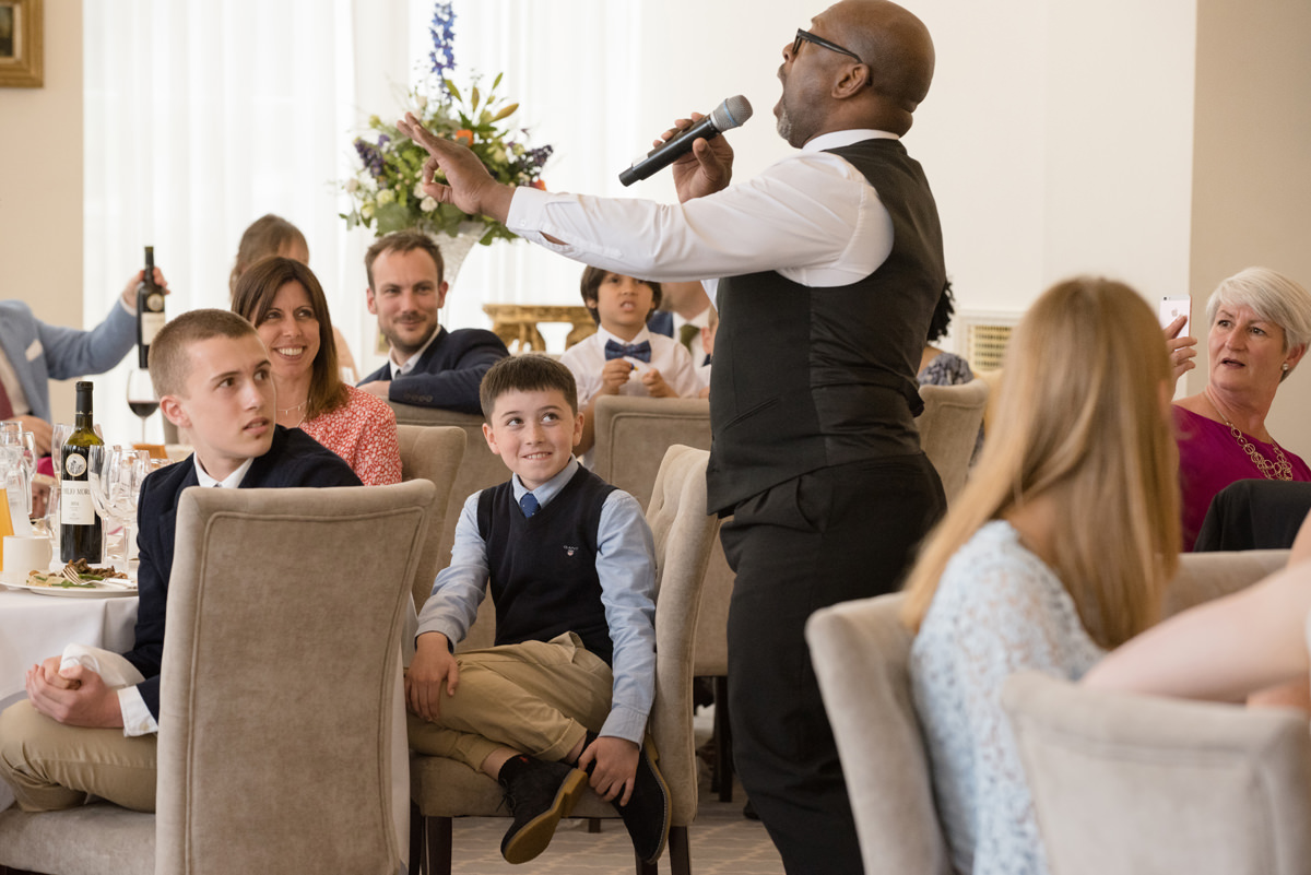 Wedding guests enjoying a performance by surprise singing waiters at Rushton Hall