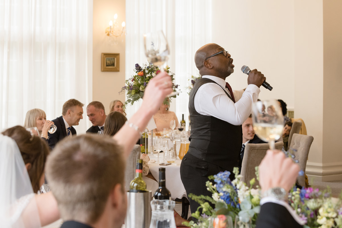 Bride and groom raising their glasses to singing waiters at Rushton Hall in Kettering