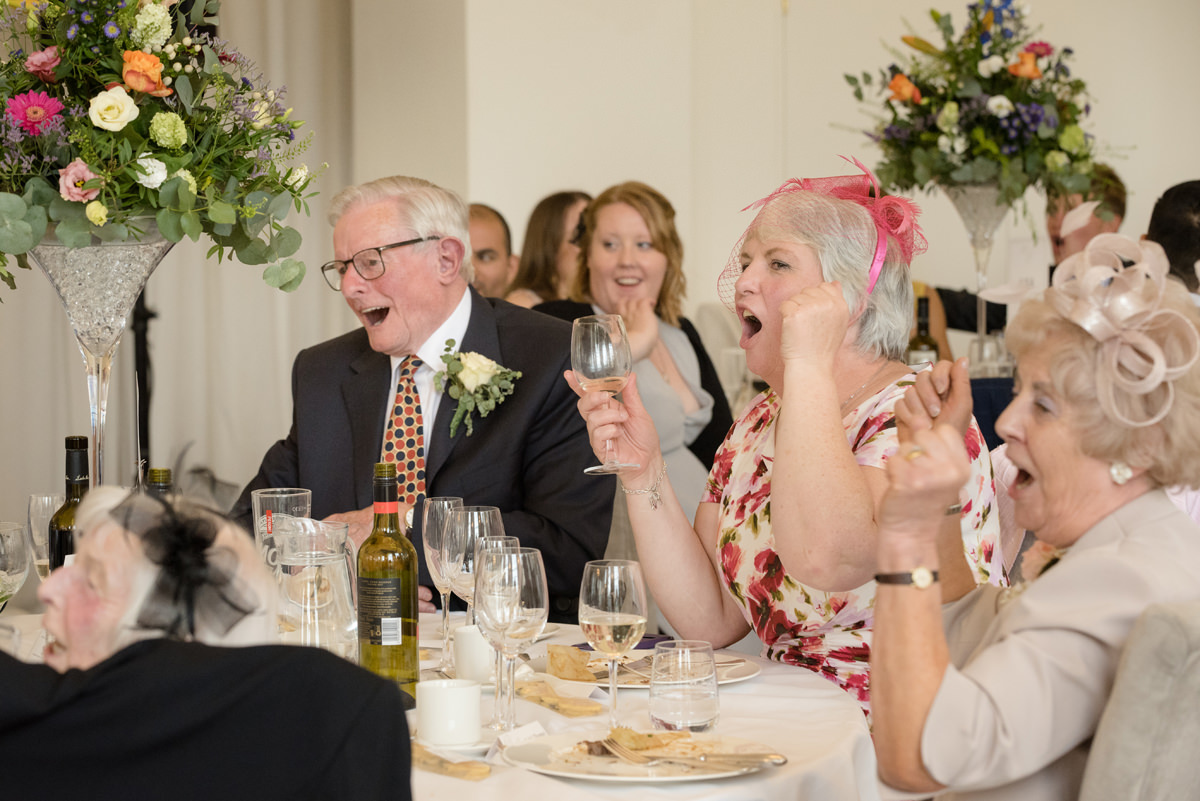 Wedding guests cheering for surprise singing waiters at Rushton Hall in Kettering