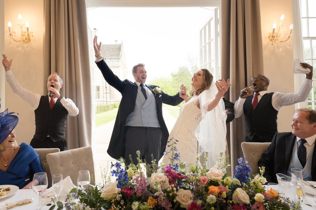 Bride and groom joining in with singing waiters' finale at Rushton Hall in Kettering
