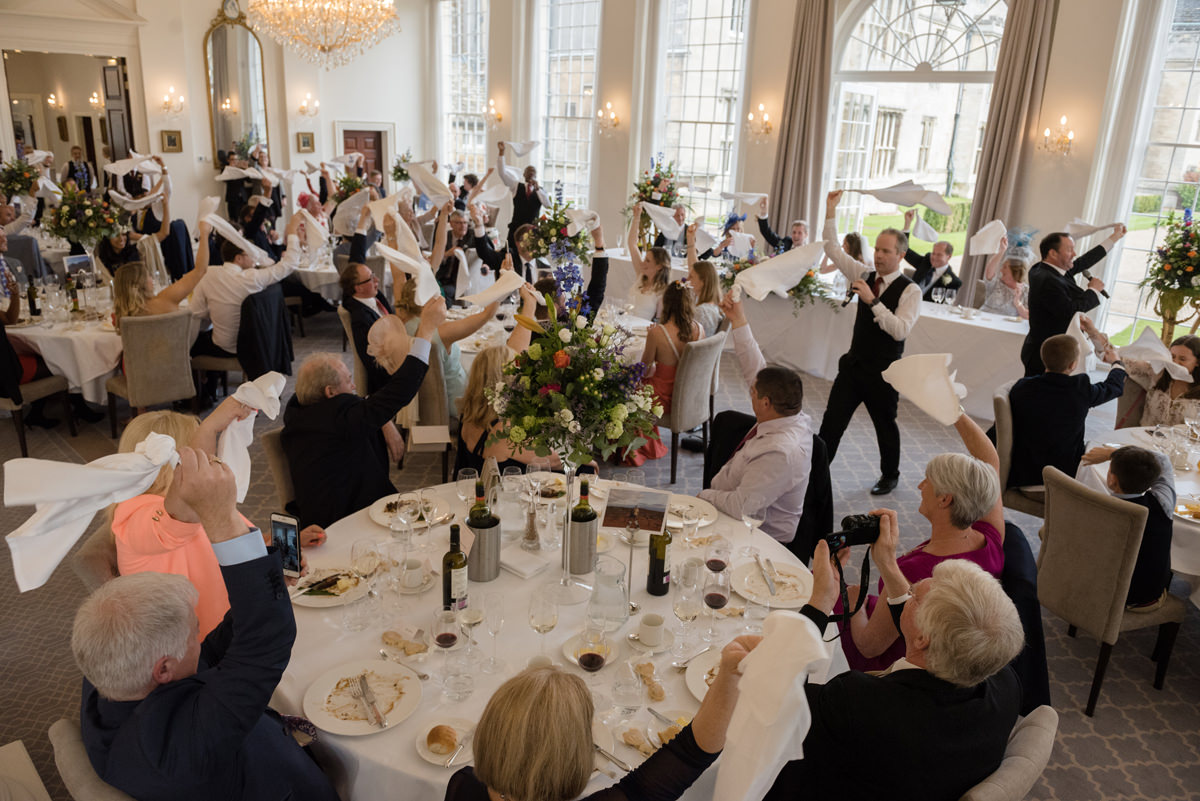 Entire room of guests waving flags as part of singing waiters performance at Rushton Hall