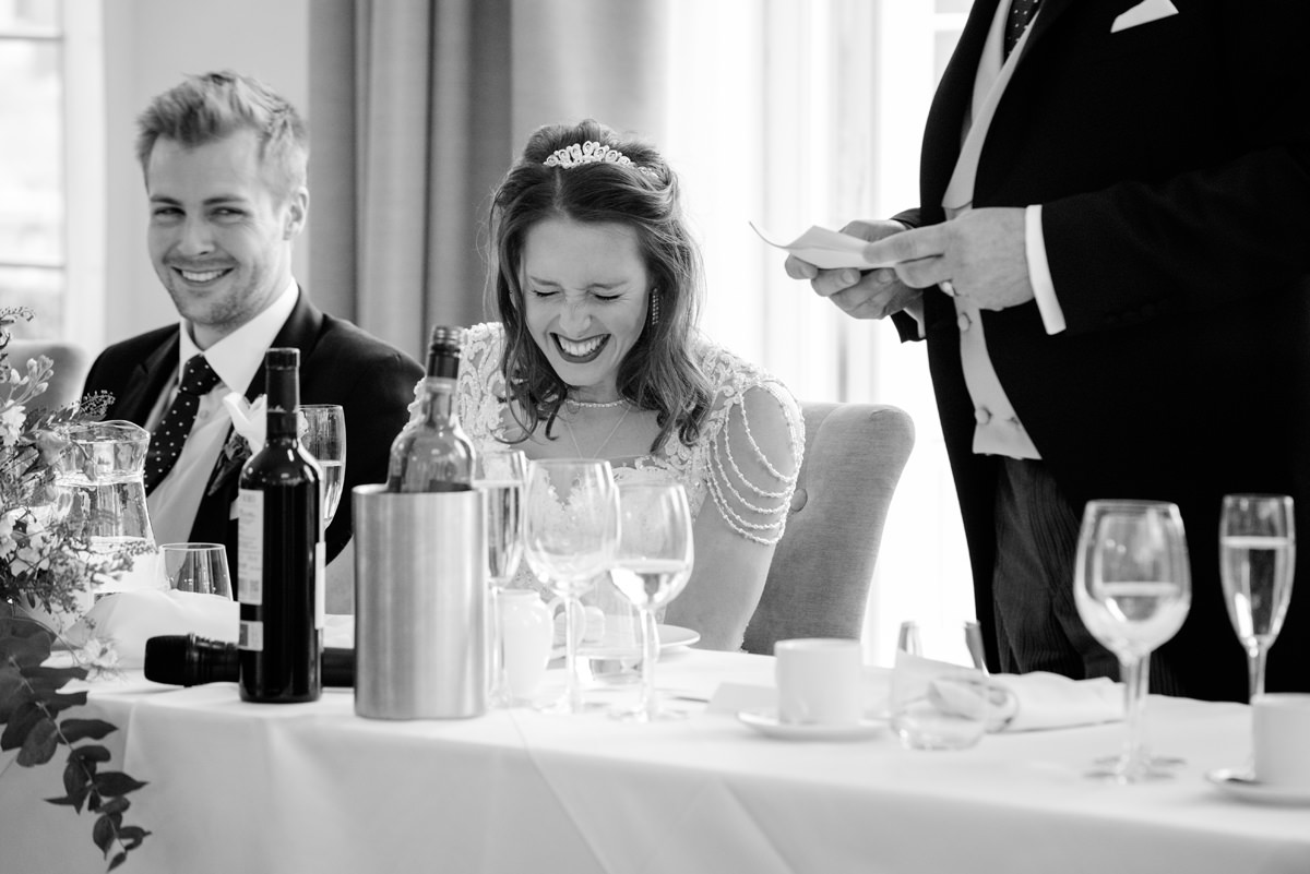 Bride laughing at dad's speech at Rushton Hall in Kettering