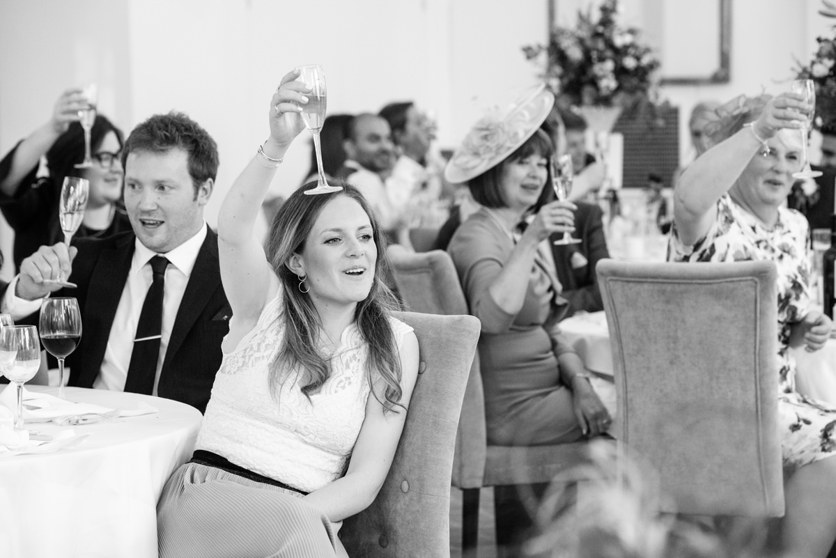Wedding guests raising their glasses at Rushton Hall in Kettering