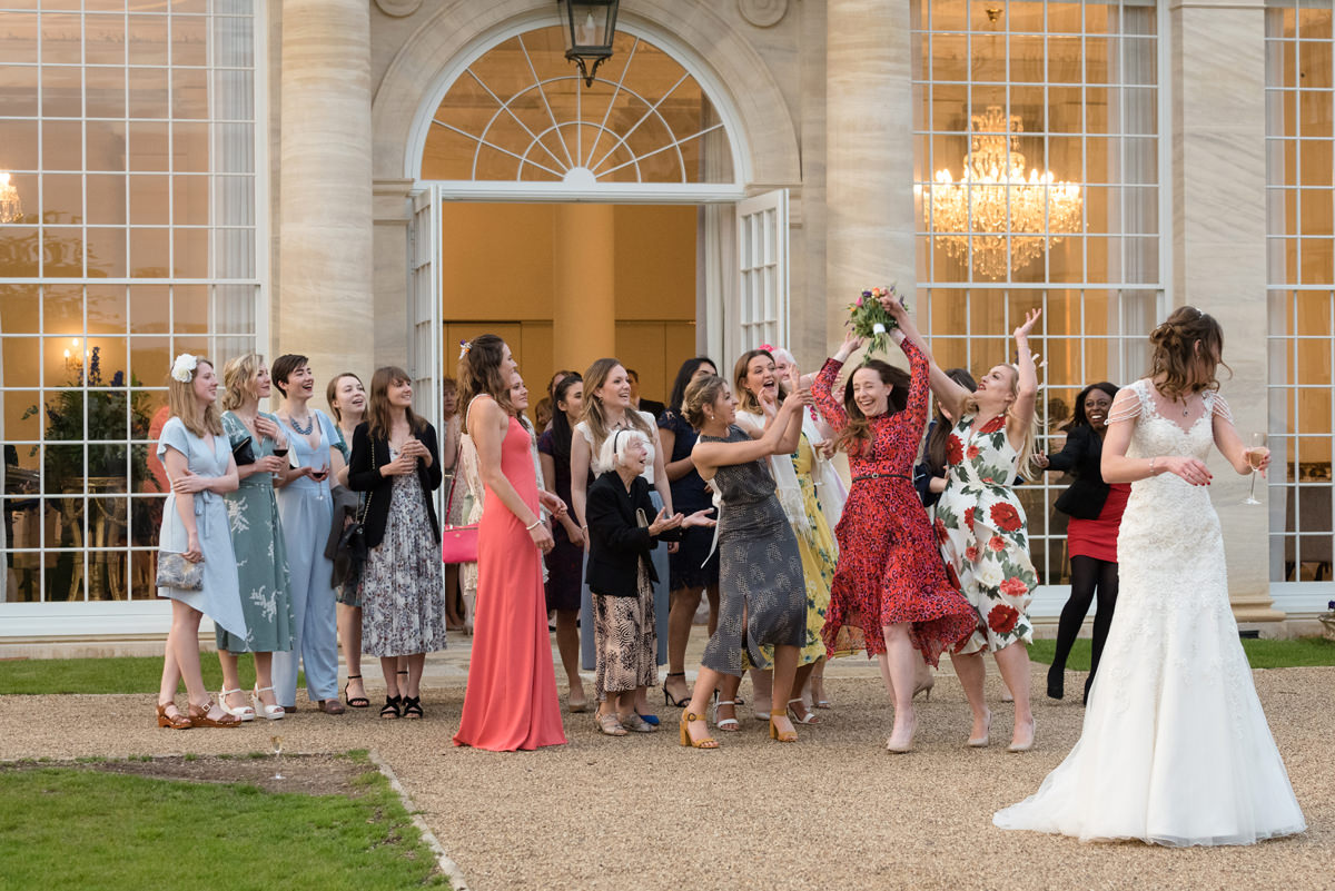 Bride throwing bouquet outside the orangery at Rushton Hall in Kettering