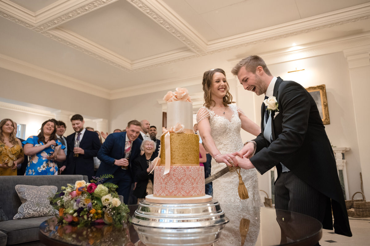Cutting the wedding cake with a ceremonial sword in the orangery at Rushton Hall