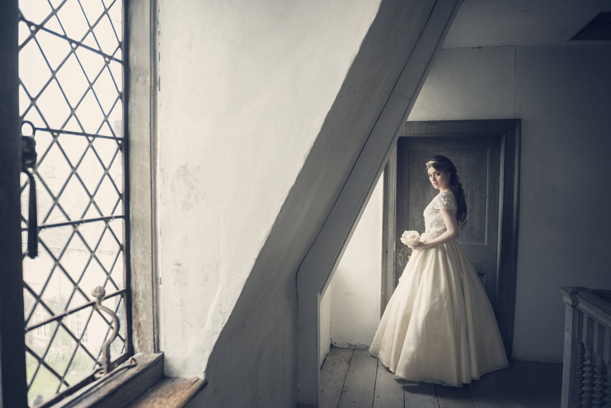 Bride posing for a photo in the attic at Boughton House