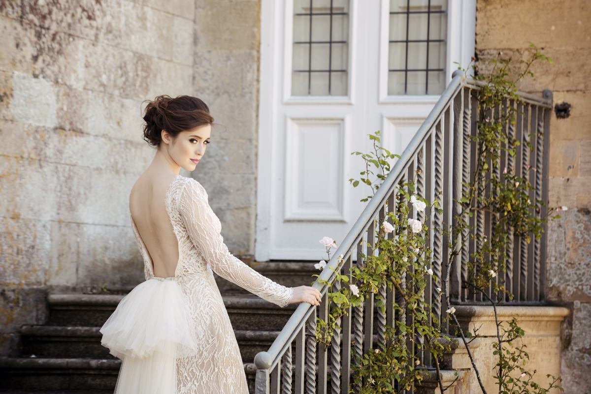 Bride posing on the steps at Boughton House