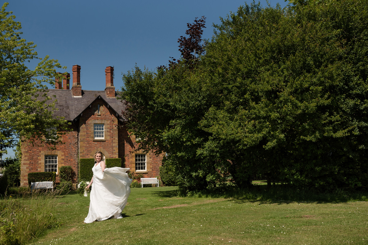 Bride twirling her dress in front of the house at Sywell Grange in Northampton
