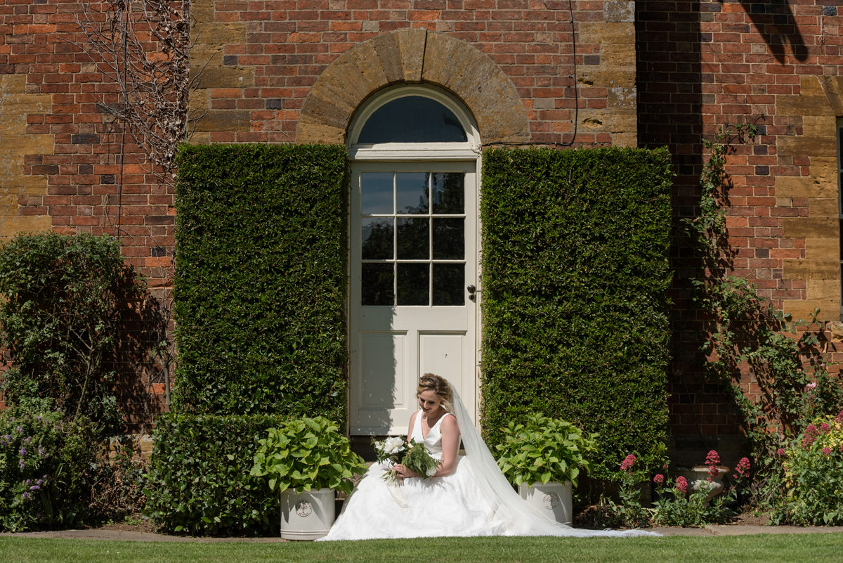 Bride sitting by the front door of the house at Sywell Grange in Northampton