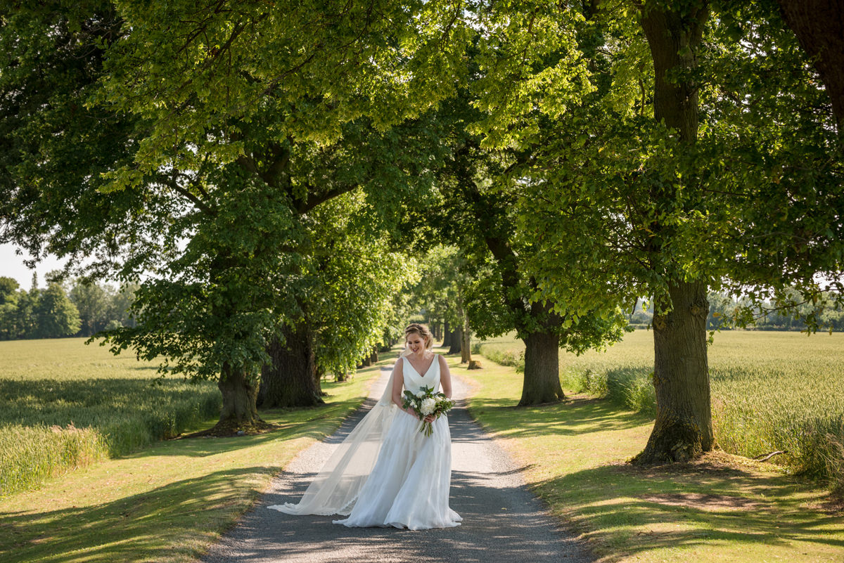 Bride walking down the drive at Sywell Grange in Northampton