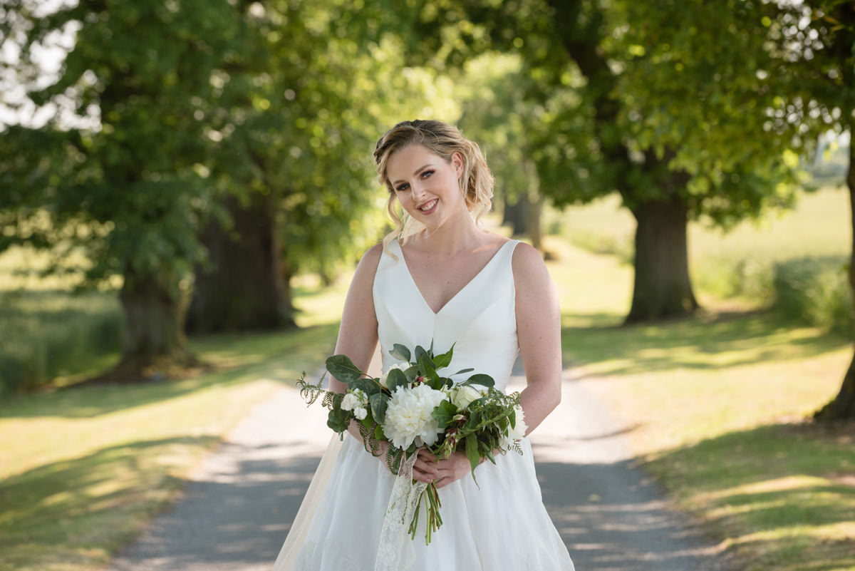 Portrait of a bride on the tree-lined driveway at Sywell Grange in Northampton