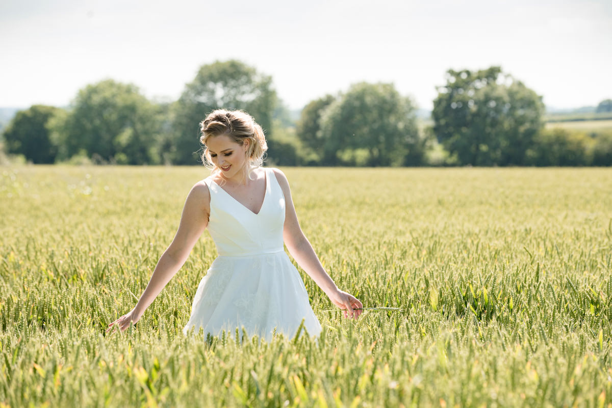 Bride walking through the cornfield at Sywell Grange in Northampton