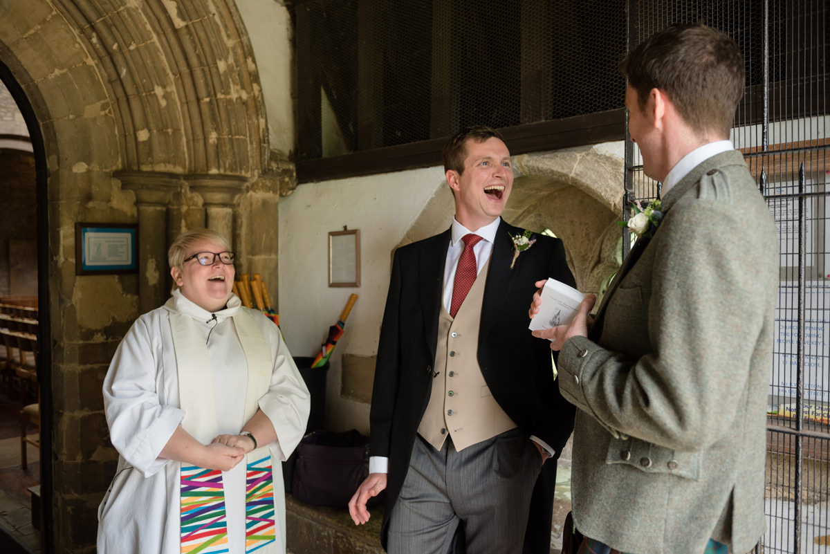 Groom laughing with the Vicar and his Best Man at Geddington church