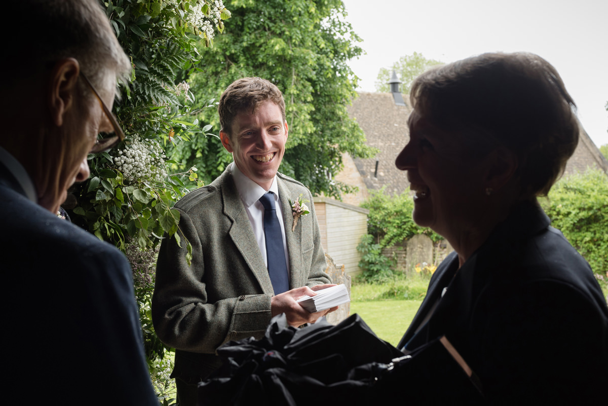 Usher greeting wedding guests at St Mary's church in Geddington, Northants