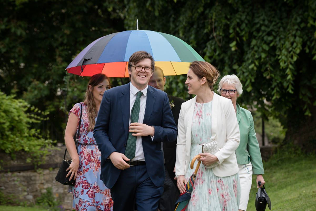 Wedding guests arriving in the rain at St Mary's church in Geddington, Northants