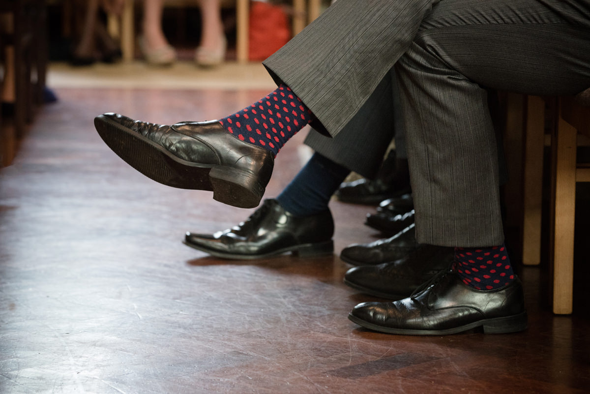 Close up photo of groom's spotted socks at St Mary's church in Geddington, Northants
