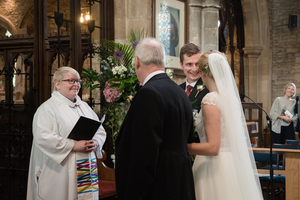 Groom greeting the bride at St Mary's church in Geddington, Northants