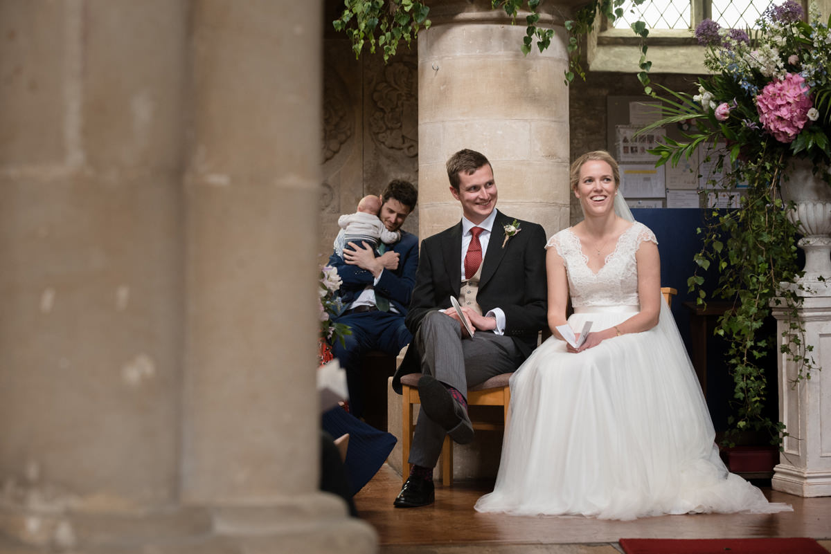 Bride and groom during the vicar's address at St Mary's church in Geddington, Northants