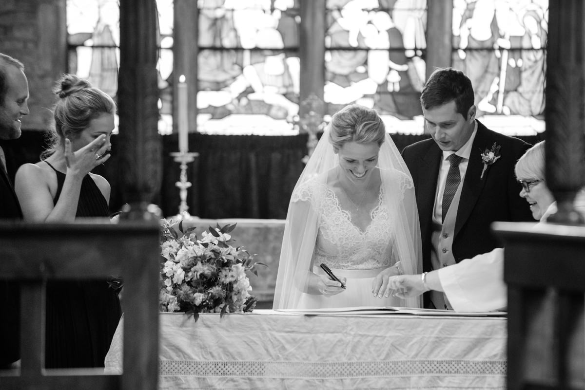 Bride signing the register at St Mary's church in Geddington, Northants