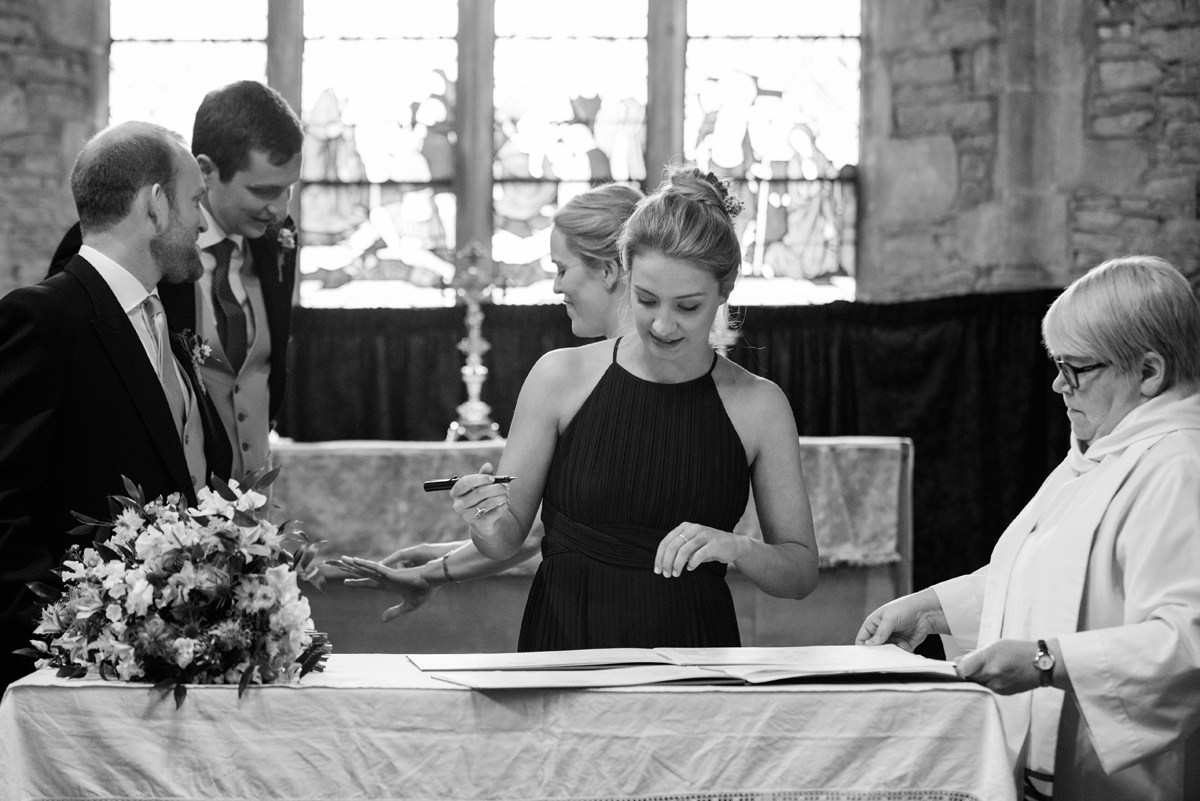 Witness signing the register at St Mary's church in Geddington, Northants