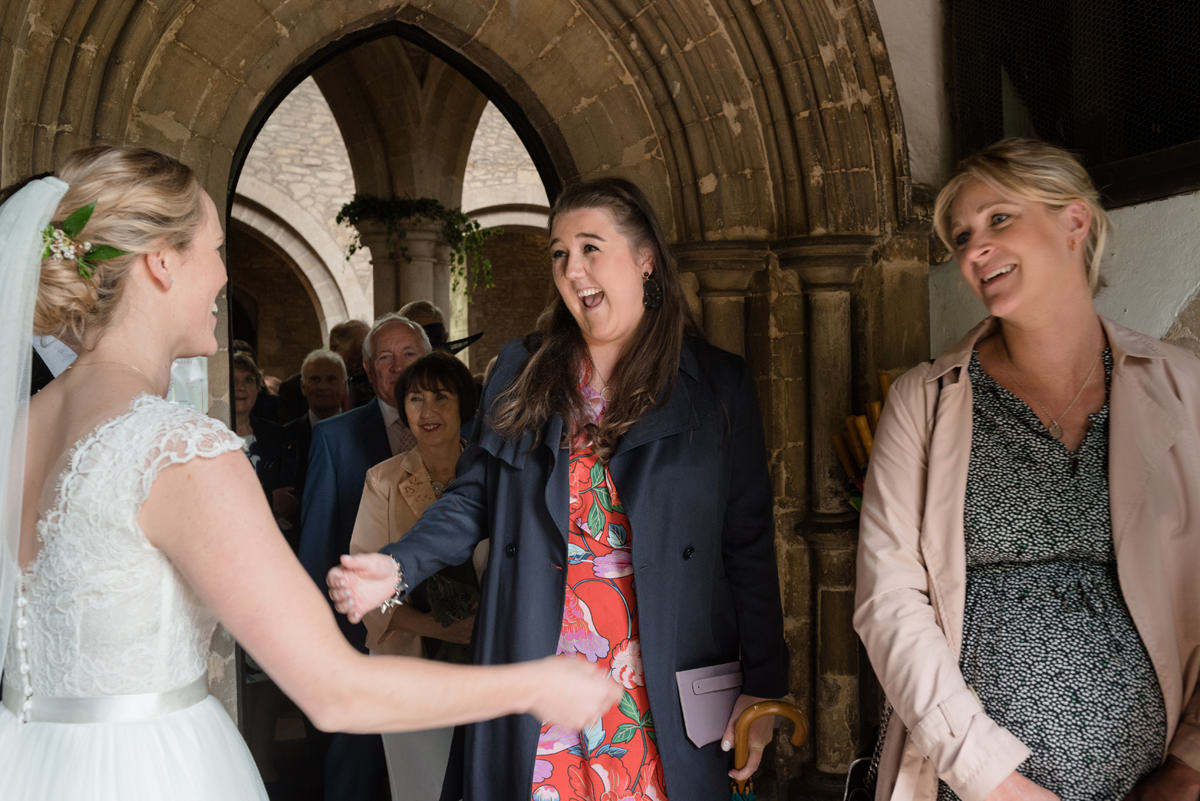 Bride greeting her cousin at St Mary's church in Geddington, Northants