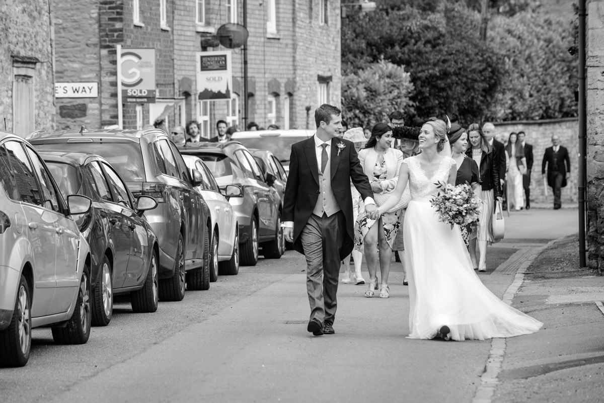 Bride and groom leading their guests through Geddington village in Northants