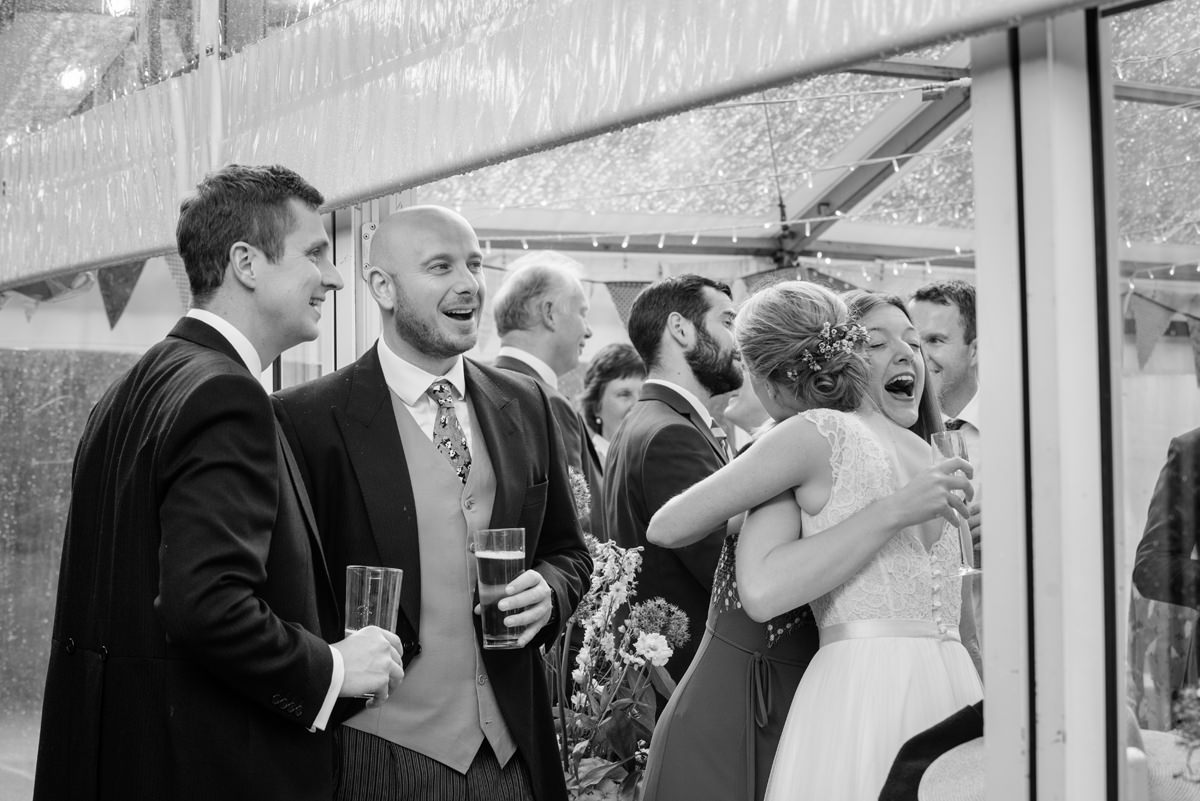 Wedding guests sheltering in a marquee while it's raining