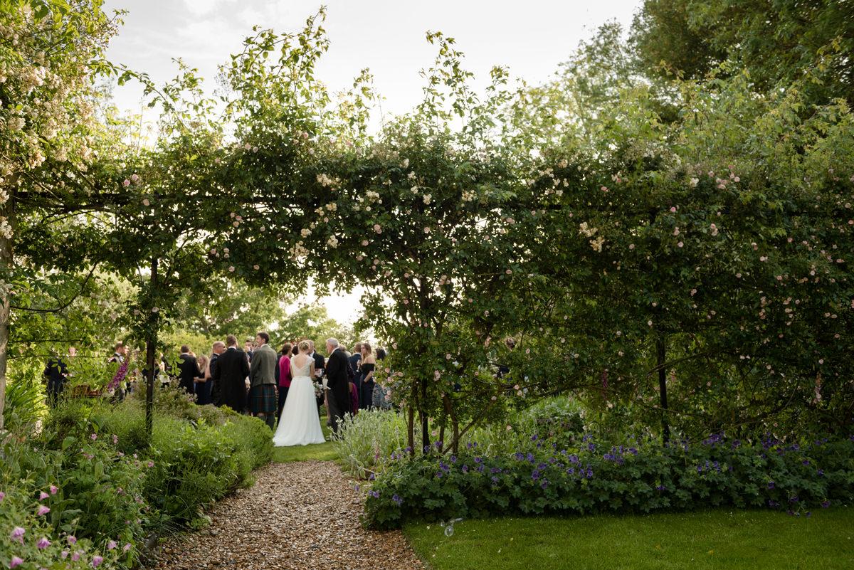 View through rose arch at a garden wedding in Geddington, Northants
